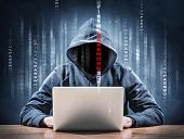 stock photo of theft  - picture of an hacker on a laptop - JPG