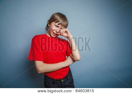 Boy, teenager, years  twelve red in T-shirt, hand wipes tears, s