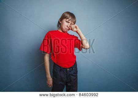 Boy, teenager, twelve years in the red T-shirt, hand wipes tears
