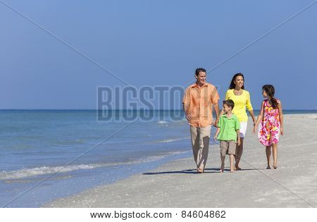 A happy family of mother, father and two children, son and daughter, walking and having fun in the sand of a deserted sunny beach
