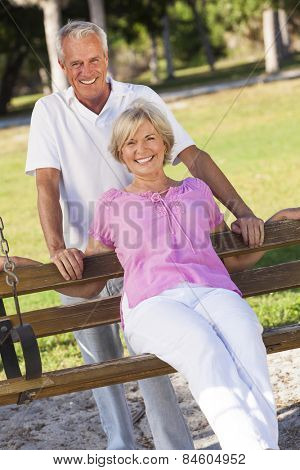 Happy senior man and woman couple sitting together outside in sunshine on a park bench