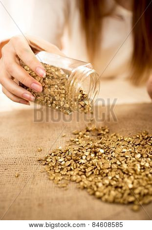 Woman Emptying Bullion With Gold On Burlap