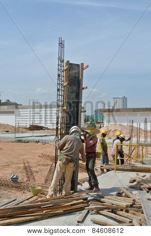 Construction workers installing the column timber formwork