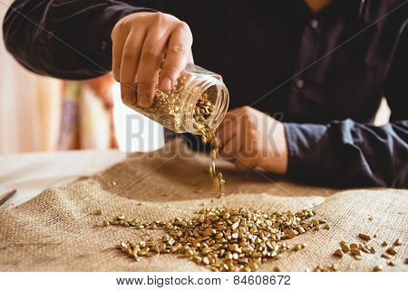 Male Miner Sitting At Table And Pouring Gold Out Of Glass Jar