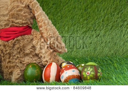 Rabbit, Sit On Green Grass And Group Of Colorful Eggs Are Behind, Can Use As Background For Happy Ea