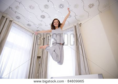 Portrait of a young happy woman jumping on the bed
