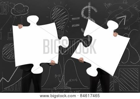 Two Business People Assembling Blank White Jigsaw Puzzles With Doodles