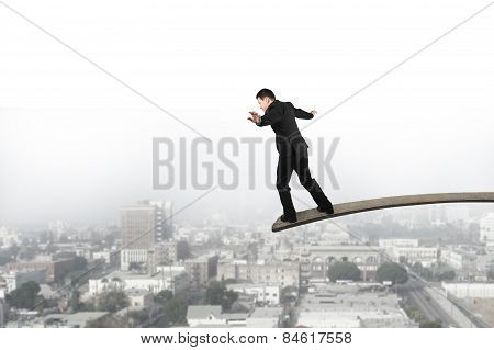Businessman Balancing On Wooden Board With Urban Scene