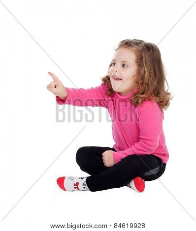 Cute little girl sitting on the floor pointing something with the finger isolated on a white background