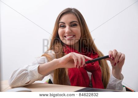 Portrait of a smiling young woman sitting at the table with stylus