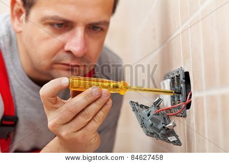 Electrician Checking Wall Fixture With Voltage Tester