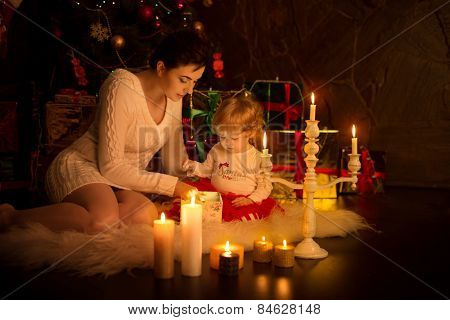 Beautiful baby girl with mother near a Christmas tree with gifts
