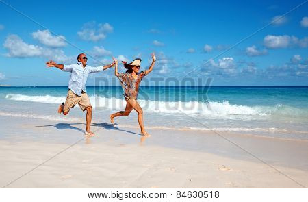 Happy couple running on the beach. Crazy vacation
