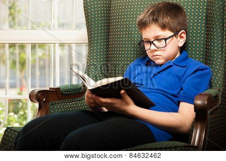 Little Blond Boy Reading At Home