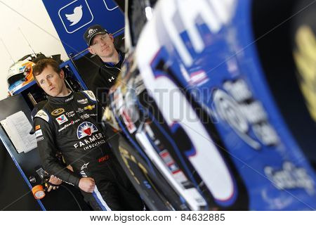 Daytona Beach, FL - Feb 18, 2015:  Kasey Kahne (5) watches his crew work on his car during a practice session for the Daytona 500 at Daytona International Speedway in Daytona Beach, FL.