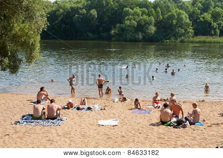 People Sunbathing And Swimming On The Beach