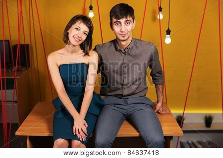 Happy young couple sitting on the desk in office