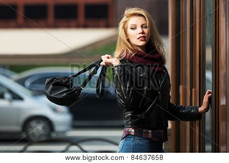 Young fashion blond woman with handbag at the mall door