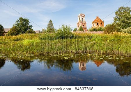 Russian Landscape With Small Tranquil River And Old Church In The Background