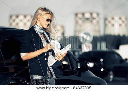 Fashion business woman with financial papers next a car