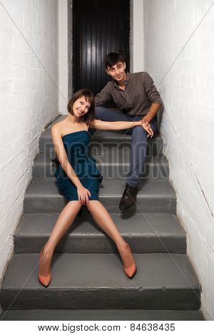 Happy young couple sitting on the steps in office