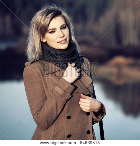 Happy young fashion woman against a morning autumn landscape