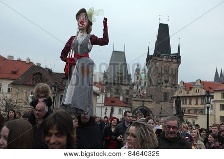 PRAGUE, CZECH REPUBLIC - APRIL 30, 2013: Participants of the costumed parade at the Witches Night carry a straw witch over the Charles Bridges in Prague, Czech Republic.