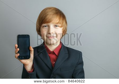 Young boy at the phone, isolated over gray
