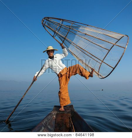 Myanmar travel attraction landmark - Traditional Burmese fisherman balancing with fishing net at Inle lake in Myanmar famous for their distinctive one legged rowing style, view from boat