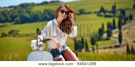 Young beautiful italian woman sitting on a italian scooter in tuscany outdoor