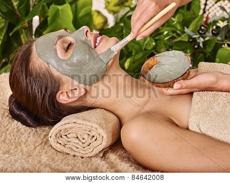 Woman with clay facial mask in beauty spa. In background tropical plants