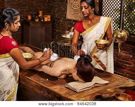 Woman having ayurvedic massage with pouch of rice. Passage to India