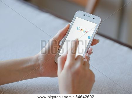 ZAPORIZHZHYA, UKRAINE - NOVEMBER 21, 2014: Young Woman Using Google Web Search on her Smart Phone.