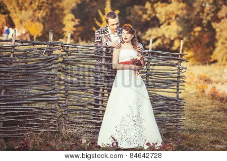Newlyweds Standing Near The Wicker Fence