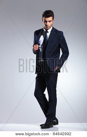 Full length picture of a handsome young business man pulling his jacket while holding one hand in his pocket.