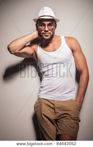 Handsome young casual man holding one hand behind his neck while leaning on a white wall with his hand in pocket.
