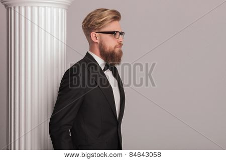 Side view picture of a elegant blonde business man posing near a white column.