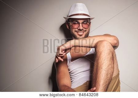 Handsome young casual man sitting and leaning on a white wall, resting his arm on his knee while smiling at the camera.