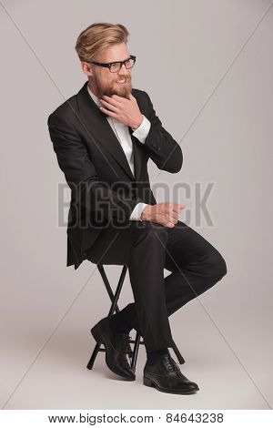 Elegant business man sitting on a stool, smiling away from the camera while fixing his beard.