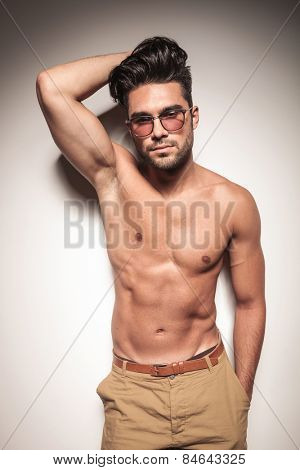 Hot sexy young man leaning on a white wall while holdinh one hand on his heair and the other one in his pocket.