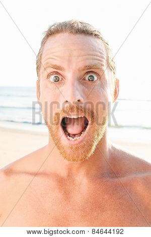 Close up Facial Expression of a Shocked Bare Handsome Man with Wide Open Eyes and Open Mouth. Captured at the Beach.