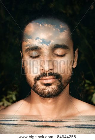 Double exposure portrait of a man combined with a photograph of a sea and clouds