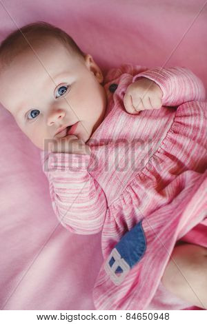 Portrait of very sweet little girl with her finger in her mouth.
