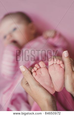 Caring hands of mother tenderly holding a tiny baby's legs.