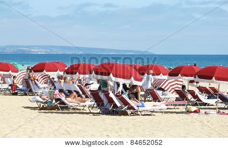 Vacationers Enjoying In The Sun At The Beach