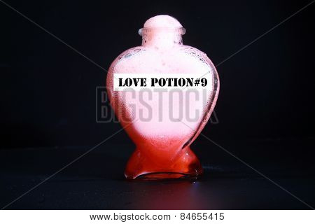 A Genuine Secret Recipe Love Potion in a Heart Shape Bottle isolated on black with room for your text