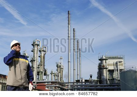 oil worker in front of large oil and gas refinery