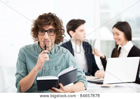 Casual businessman holding notebook with his business team on background