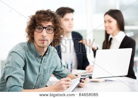 Young businessman using notebook with his business team on background