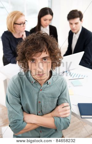 Businessman looking at camera with his business team on background